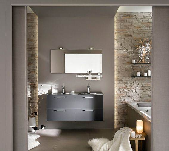 Avec son meuble-vasque aux façades en verre gris et ses murs revêtus de fausse pierre, cette salle de bains joue le naturel chic et urbain. ...