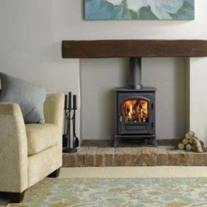 Wood burner with wooden mantle and brick base.