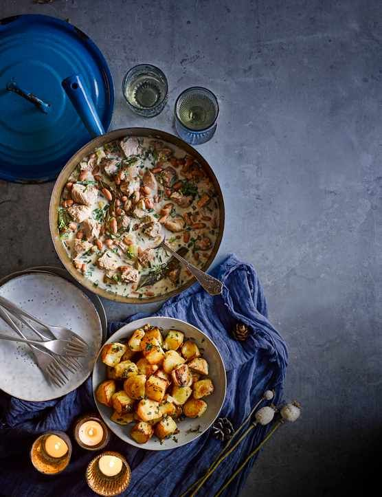Pork shoulder with tarragon and borlotti beans  This warm and wintery Italian-style stew is perfect for a festive feast. You can serve it with creamy mash but the crunchy mini roasties really are special