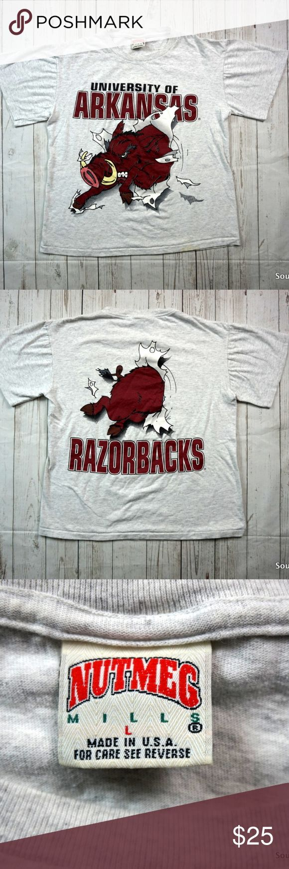 "Vintage 90s Arkansas Razorbacks T-Shrit By Nutmeg Vintage 90s Arkansas Razorbacks T-Shrit, Men's Large, Break Through Double Sided Logo, University of Arkansas, Nutmeg Mills  Brand: ......... Nutmeg Color: .......... Heather Gary Size: ............Men's Large Material:  ..... 100% Cotton  Measurements: Sleeves: ...................... 7"" inches Chest: ....................... 22"" inches Length: ...................... 30"" inches  Ships in 24 hrs or less from a clean smoke free environment…"