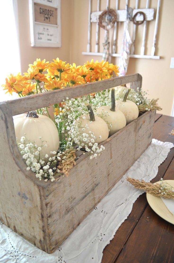 A modern farmhouse centerpiece is easy to achieve with an old bottle holder, some flowers and a few white pumpkins. Perfect for fall entertaining.