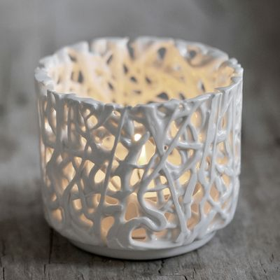 Tangled Web Tealight Holder by Timea Sido Contemporary Ceramics  -  This beautiful tealight holder creates a magical ambiance as the candlelight shines through the intricate gaps of the 'tangled' pattern. This special piece will bring detail and elegance to your wedding table setting, creating a romantic mood for your extraordinary day. Each piece is individually hand crafted by Timea Sido using fine white earthenware with an off white gloss glaze finish.