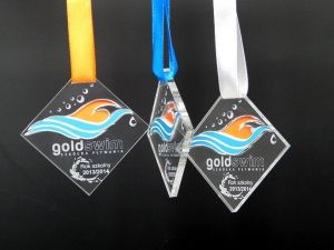 Kolorowy medal z pleksi przeźroczystej o nietypowym krztałcie, przeznaczony dla pływaków.