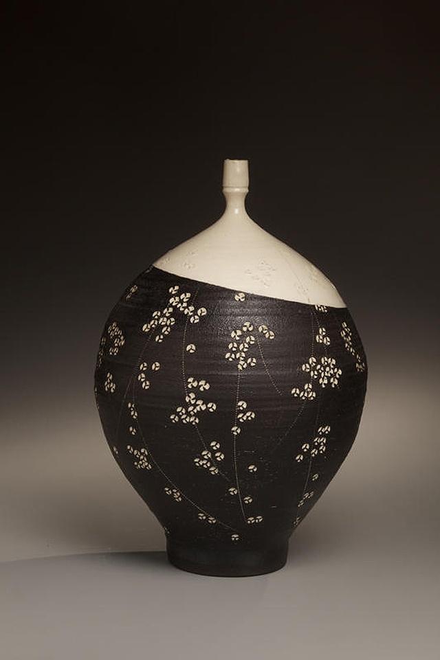 Textured black glazed stoneware vase with white glaze, impressed plum blossom patterning and white slip inlay (Inv# 6714), 1979. Kondõ Yutaka [1932-1983]. Stoneware with slip glaze, 14 1/2 x 8 5/8 inches. Courtesy of Joan B Mirviss LTD, New York / Photo by Richard Goodbody.