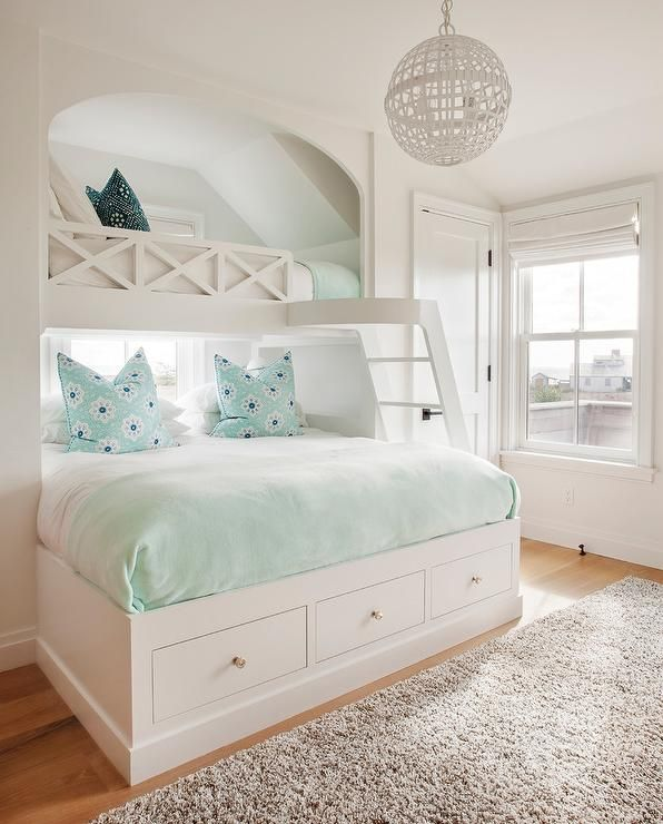 Cottage girl's bedroom features a full sized built-in bed fitted with storage drawers dressed in a mint green blanket and aqua blue pillows tucked under a loft bed with a criss cross railing illuminated by a white sphere chandelier.