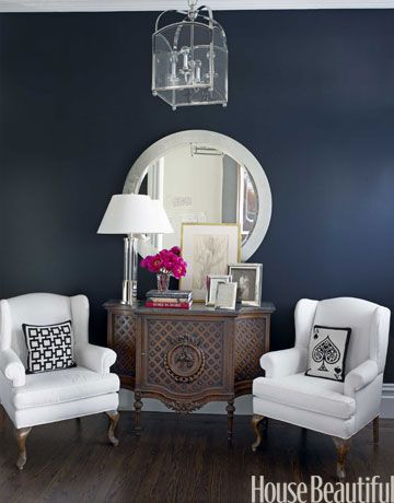 An entry wall in Ralph Lauren's Bone Black sets off vintage chairs upholstered in the simple white cotton Ken Fulk used throughout the house. Jonathan Adler pillows.