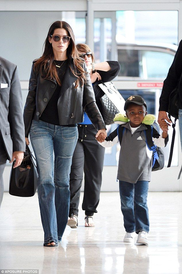 Take off: Sandra Bullock and son Louis jetted out of JFK airport in New York on Sunday...