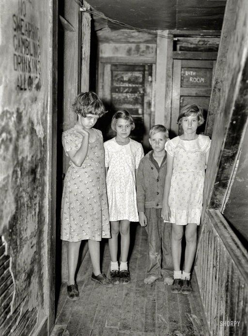 "January 1937. ""Children of citrus workers in hallway of apartment house. Winter Haven, Fla."" Swearing, Gambling and Drinking, with their little brother Allowed. Photo by Arthur Rothstein, Resettlement Administration."