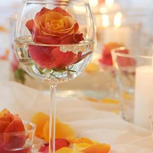flower floating in a wine glass plus pearls centerpiece (grouping of glasses in middle of table)