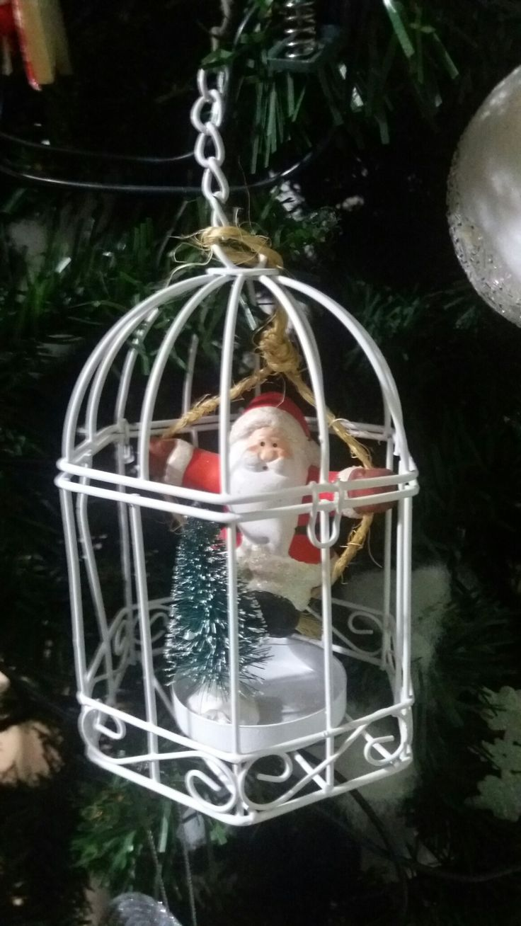 Diy. Recycle small decoration cage by adding a small tree and a Santa Claus and you will have a beautiful Christmas ornament.