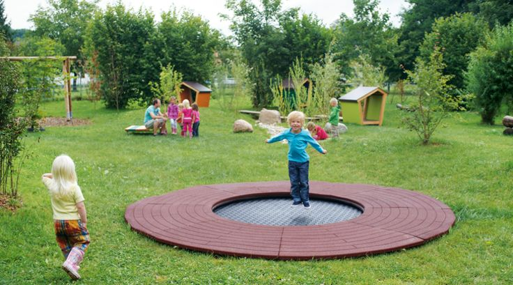 Natural Playgrounds For Preschoolers   Little boy jumping on the round playground trampoline Wehrfritz Ground ...