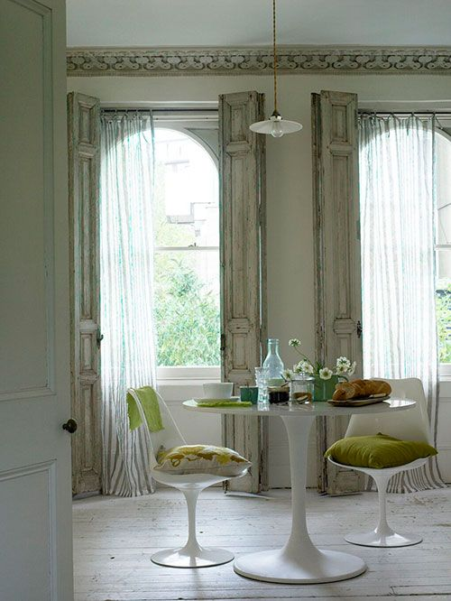 wonderfully distressed floor length shutters add drama and height. Ceiling molding matches the shutters and increases the drama.