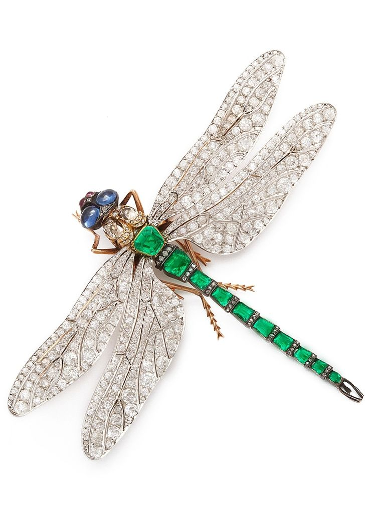Rare French Emerald and Diamond Dragonfly Brooch in the manner of Fouquet. The wings in platinum set with diamonds, and the body set with emeralds, and two cabochon sapphires for the eyes as well as cabochon rubies, in the manner of Alphonse/Fouquet, French, circa 1890.