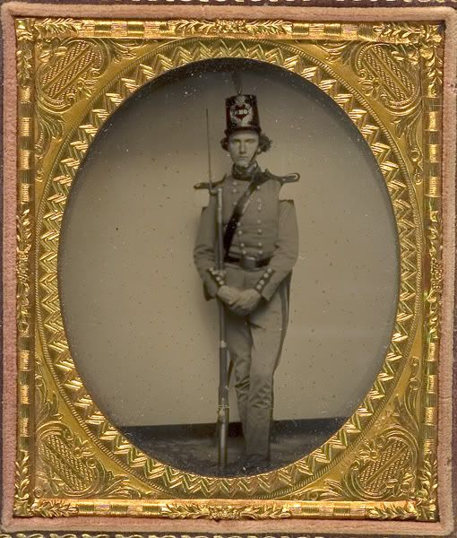 Unidentified Connecticut militiaman in grey (or possibly light blue) double breasted tailcoat and leather shako