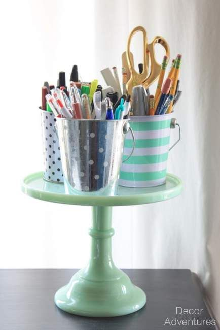 Pails on a Cake Stand for Desk Organization — Cute pen/pencil organization and love that the cake stand leaves room underneath for staplers, tape dispensers, etc. A great way to organize a desk in an office or craft room!
