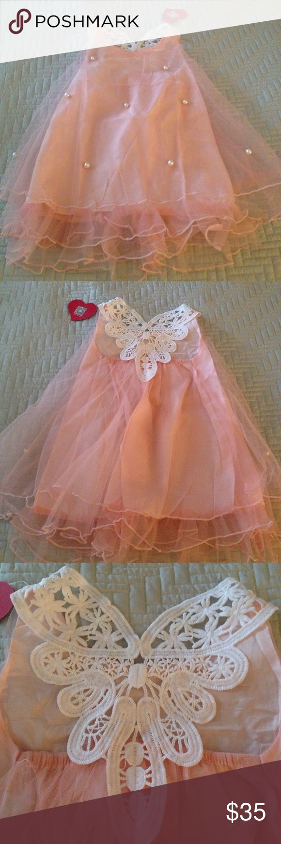 Boutique little pink dress with pearls & design Brand new size 5 unique boutique item. Size 5 but can be ordered in other sizes as well. Beautiful design in back and little pearls in front. Tiered layers. Might want to order one size up my daughter is tall for 5 and she needed a six. it is 23 inches in length. boutique Dresses