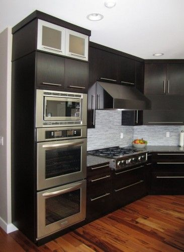 View of the double wall ovens, built-in microwave, gas cooktop, and hood.. modern kitchen