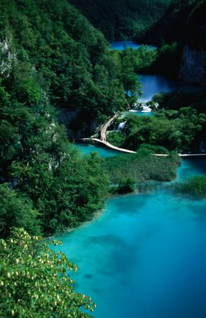 Plitvice National Park, #Croatia  Wooden walkways arcing over the surface of azure pools at the base of steep forested mountains in the Plitvice National Park.