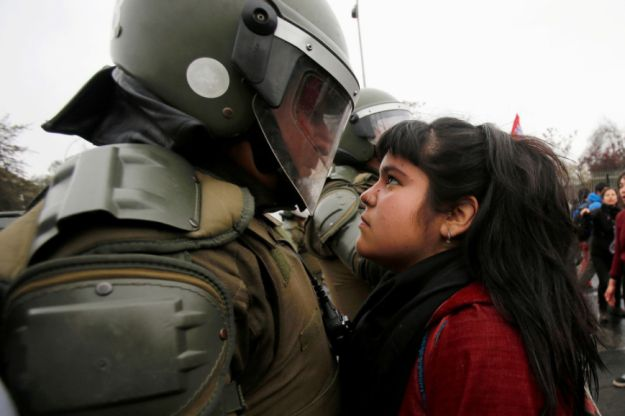 This girl who stared down a riot policeman during a protest in Chile to remember the country's disappeared. | 17 Badass Women You Probably Didn't Hear About In 2016