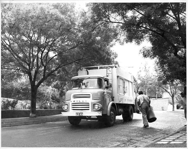PH 12849. Council worker carrying domestic rubbish bin to a Prahran Council rubbish truck.