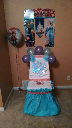 Disney Frozen theme chair for Elf on the Shelf Birthday tradition! Fold bed sheet in half and wrap around back of chair and tie. Wrap pillow case over chair cushion. Plastic table cloth cover folded in half (hot dog style) held on by glue dots. Tape snowflake bead string onto table cloth. Add princess streamer. Add bows, snowflake, Birthday tiara, and balloons. Balloons also have Hersey kisses and hugs in them.