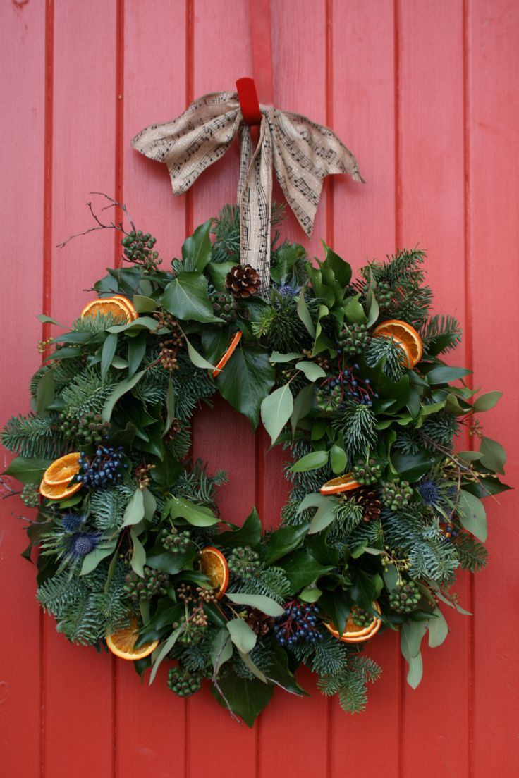 christmas wreath with ivy, viburnum tinus, eucalyptus populous, pine cones and oranges.