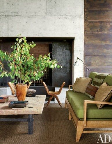 Playing with contrast on the porch of a Montana retreat, Madeline Stuart juxtaposed a stone-top table with a pair of midcentury Italian rope-and-walnut folding stools from Lawson-Fenning. The sofa has seat and back cushions of a Great Outdoors fabric by Holly Hunt; the vintage floor lamp is from JF Chen   archdigest.com