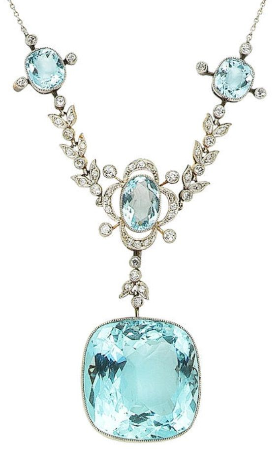 A Belle Epoque aquamarine and diamond necklace. The front composed of three delicate quatrefoil clusters, millegrain-set throughout with cushion-shaped and oval-cut aquamarines and old brilliant and single-cut diamonds, connected by similarly set single-cut diamond foliate swags, suspending a large cushion-shaped aquamarine pendant, mounted in platinum and yellow gold, pendant 3.3cm. #BelleÉpoque #necklace