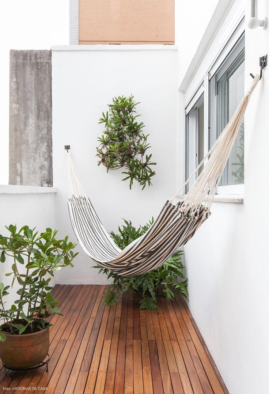 Varanda de apê em São Paulo tem deck de madeira, rede de balanço e muitas plantas.