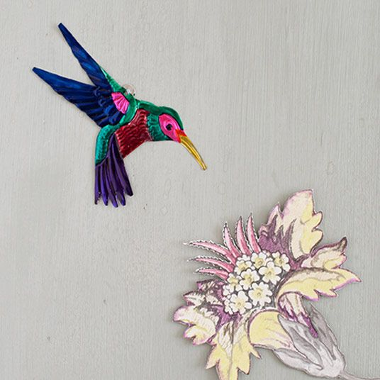Hummingbirds are such exquisite little birds. This sweet hummingbird decoration is handmade from tin and is a must for those enchanted by hummingbirds. Made in Mexico, these tin decorations are often used for protection and to bring good luck.Use as hummingbird wall art or display in a group with other bird decorations. These hummingbird decorationsmake gorgeous gifts that are easy to send in the post.Each bird has a small hole at the top for hanging.Dimensions: L 12.5cm W 7cm