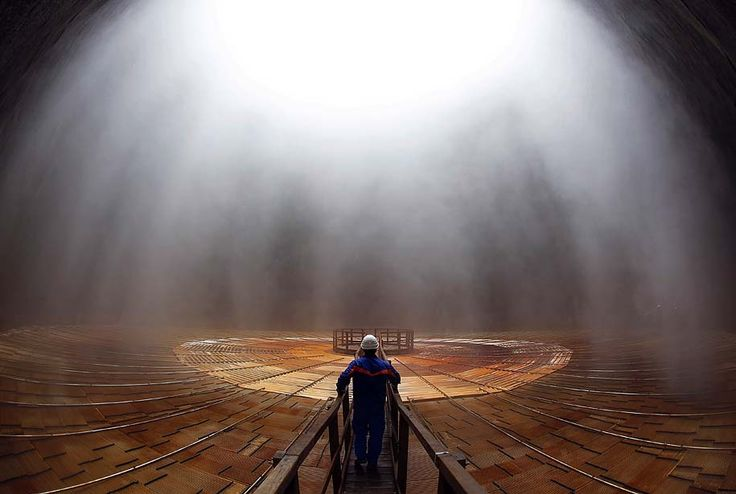 A worker inspects the interior of a cooling tower at a geothermal power station in Monterotondo Marittimo, Italy. PHOTOGRAPH BY: ALESSIA PIERDOMENICO / BLOOMBERG