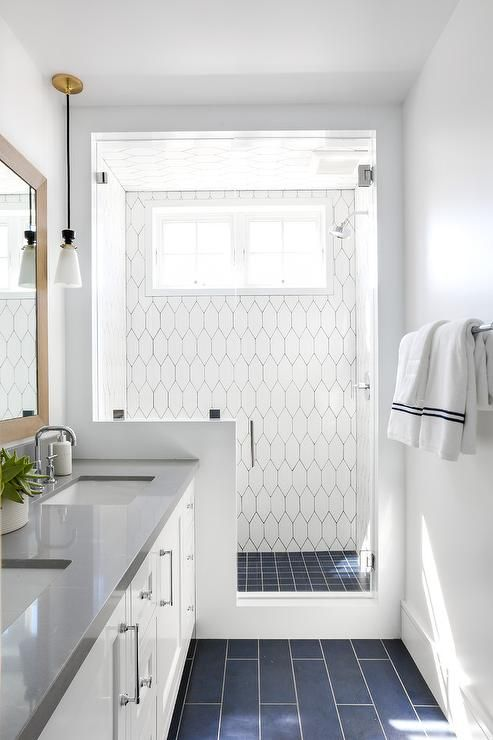 A seamless glass shower fitted with white geometric wall tiles fixed framing a window located adjacent to a polished nickel shower head located over blue grid floor tiles.