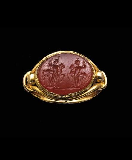 A ROMAN CARNELIAN RING STONE  -  Circa 1st-2nd Century A.D.   The slightly convex oval stone engraved with the Dioscuroi, the twins standing frontal with their heads turned towards each other and surmounted by a cruciform star, each with a spear in one raised hand, the other arm around the neck of a horse, on a groundline; mounted as a ring in a circa 1900 gold setting.