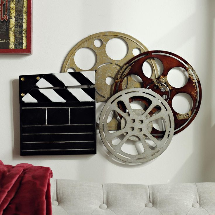 Go back to the basics of film with this Theater Room Metal Plaque. Featuring a clapboard and gold, silver and red movie reels, this piece is reminiscent of Old Hollywood. It's perfect for your media room, theater room or bonus room!