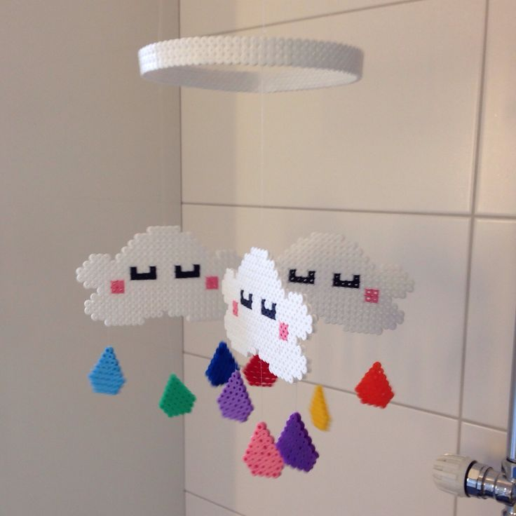 A kawaii cloud 'n' raindrops mobile hanging over our changing table