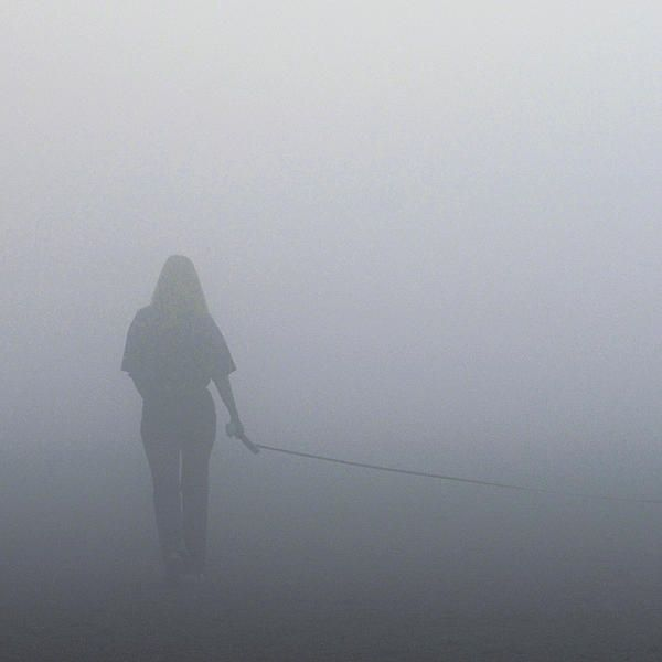On a foggy morning at the beach in Toronto, a dog appeared in front of me, followed by its long leash, and finally by its owner. After they walked by, I stopped, turned around, and took a few photos as they moved further into the fog. In this one, the dog was just out of view, and so the woman appears to be walking an invisible dog, or perhaps she is walking the fog.  Maybe the fog is walking her. #fog, #dog, #woman