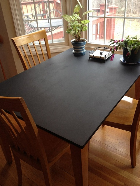 Chalk board painted kitchen table. This would be a good idea for a kid's craft table, I don't know about chalk and eating area