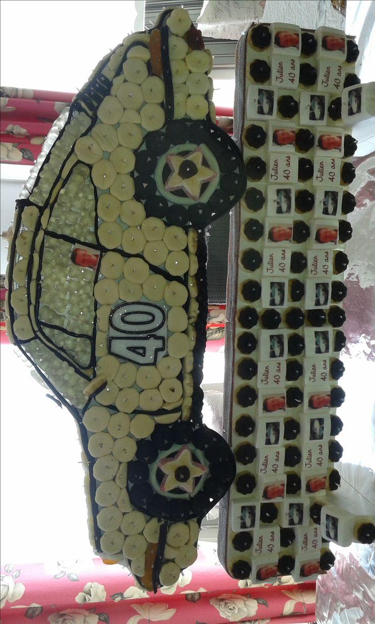 Pour les 40 ans de mon fils, j'ai voulu lui reproduire sa porsche. Support en polystyrene commandé sur internet ainsi que chamallows avec photo. Réalisé avec des bonbons vanille, coca Haribo, des rouleaux de zan, et des bonbons fruités pour les roues..