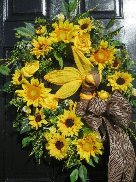The focal point of this handmade spring summer wreath for your front door is a yellow and brown bumble bee made of a heavy duty paper. Mr. Bumble Bee is upright with 4 large spread wings. The base is an 18 grapevine wreath to which I have added 2 types of sunflowers; one with yellow centers and one with dark brown centers. Also added are yellow silk ranunculus, spring boxwood with yellow flowers, and green boxwood. Surrounding all this yellow loveliness are ficus leaves. An XL bow is…