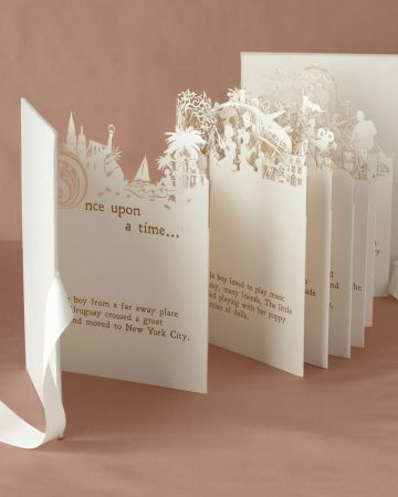 "An accordian-style booklet displaying the couple's love story in ""story book"" form"