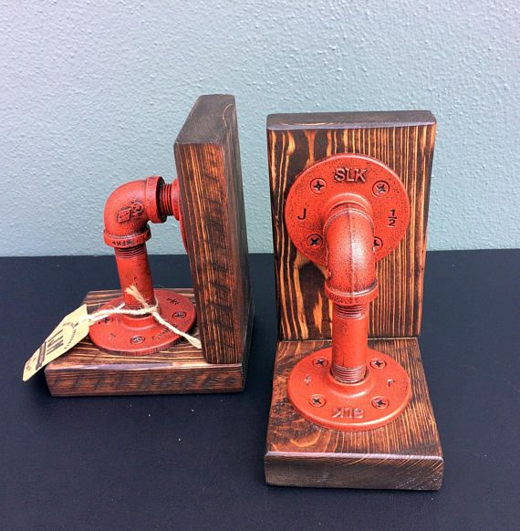 "Industrial Bookends (pair). Constructed of ½"" iron pipe with a CUSTOM finish mounted on wood supports. This industrial pipe set of bookends is an excellent industrial accent for your home or office. Dimensions: 6 Tall x 5"" Width Our products are hand-crafted with a careful eye to"