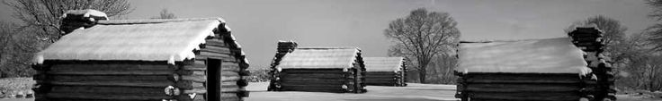Log huts are coated in a fresh layer of snow. Valley forge
