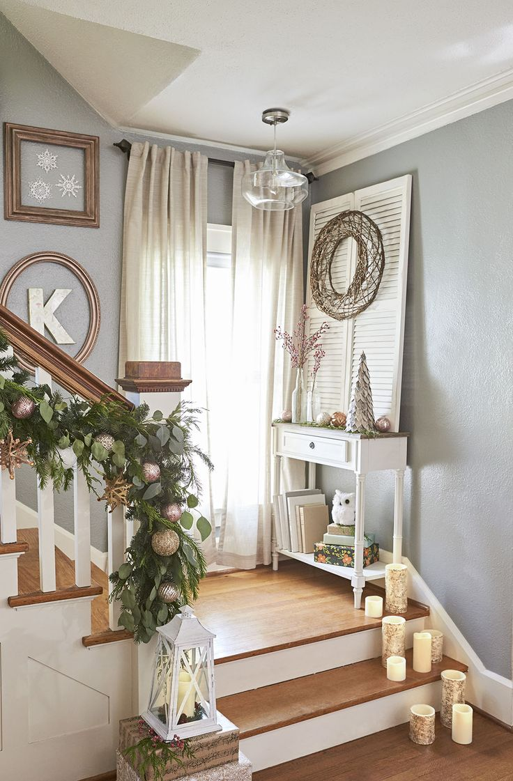 Stair landings are good spots for holiday decor. Set out lanterns and LED candles for extra glimmer, and adorn existing pieces, such as the branch wreath gracing an existing decorative shutter.