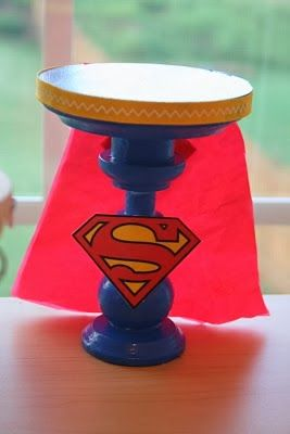 DIY Super Heroes Cupcakes Stand. To make this  base = stand for cupcakes or cakes just put a shield of your favourite Superheroe in the front,  or the one the party is themed. Add a cape made of rush paper or tissue paper and...you have it!