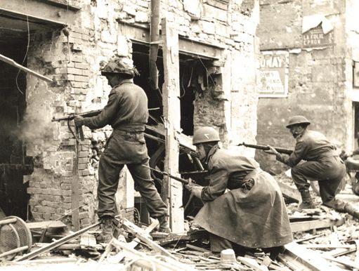 Caen 10 juillet 1944, des soldats canadiens procèdent au nettoyages des maisons pour éliminer les éventuels snipers ennemis. On peut remarquer que l'homme qui tire par la porte utilise un MP40 allemand. (Conseil Regional de Basse-Normandie / National Archives Canada).