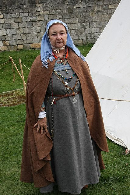 Appears to be a tube-shaped apron dress belted.  Note the fringed veil over a coif, the patterned silk cut into strips for trim at the neck and sleeve-ends, the leather belt, and the fact that the shawl/cloak appears to tie on at the neck with beaded thongs.  My guess is that the lady is attempting to recreate a Viking age lady in Ireland.