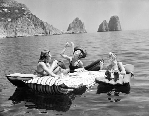 Three young women eat spaghetti on inflatable mattresses at Lake of Capri, 1939