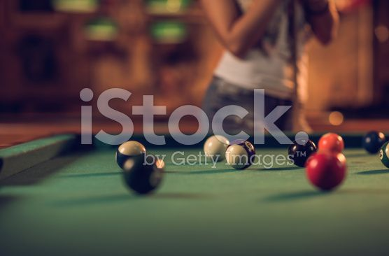 Pool balls on a table with unrecognizable person in background. royalty-free stock photo