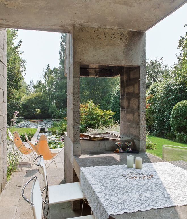 The dining room leads onto a terrace with a built-in concrete table and barbecue that are original to Raman and Schaffrath's design. A pair of Hardoy butterfly chairs from Knoll are positioned by the pond. Photo by Frederik Vercruysse.