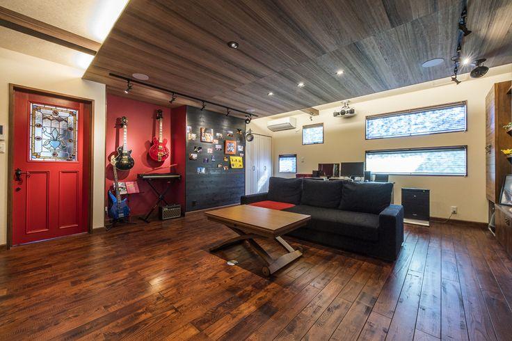 ステンドグラスの真っ赤なドア、ご夫婦のこだわりのオーダー品です。 赤色を隣の壁に連続させて、ご主人様のご趣味の楽器展示スペースに。 その隣には、写真や絵をランダムに壁掛けしてギャラリーに仕立てました。  #家づくり #リビング #ldk #インテリア #interiordesign #interior #リビングインテリア #デザオ建設